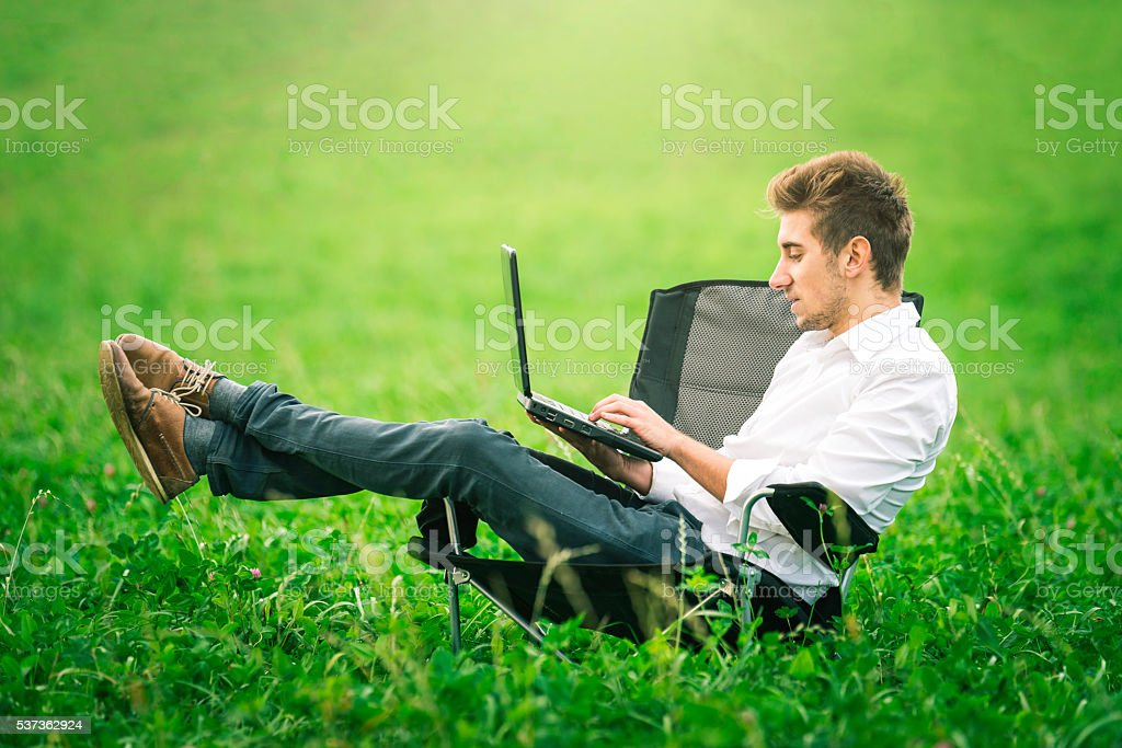 Businessman sits in an office chair in a field stock photo