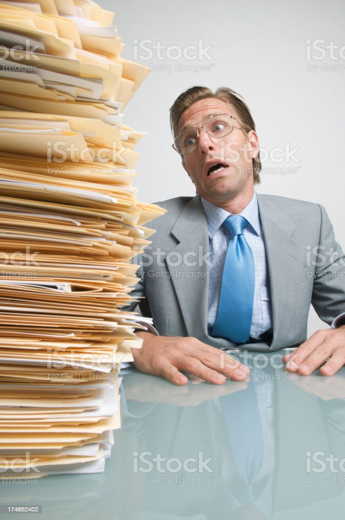 Businessman Sits Looking Frightened by Pile of Paperwork stock photo