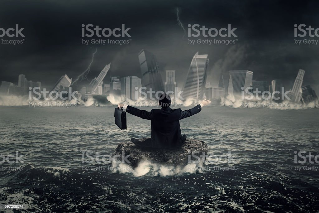 Businessman sits on the rock at sea royalty-free stock photo