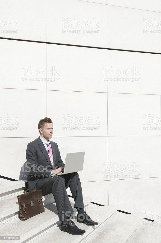 Businessman Sits on White Steps w Laptop royalty-free stock photo