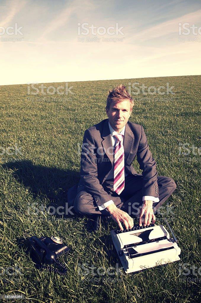 Businessman Sits Typing on Old Typewriter royalty-free stock photo