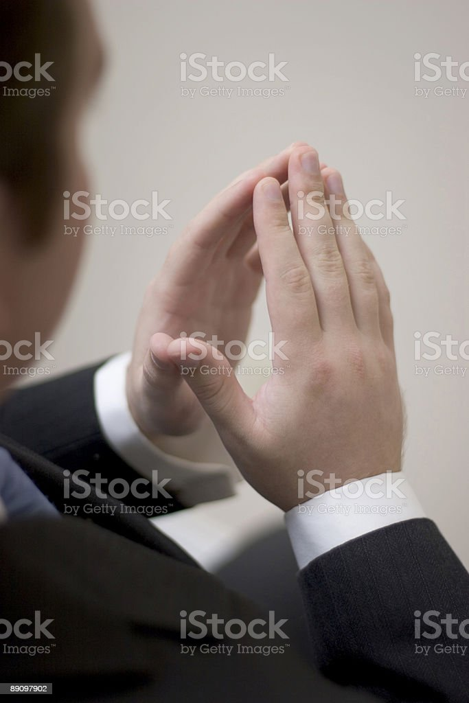 Businessman sits with hands together royalty-free stock photo