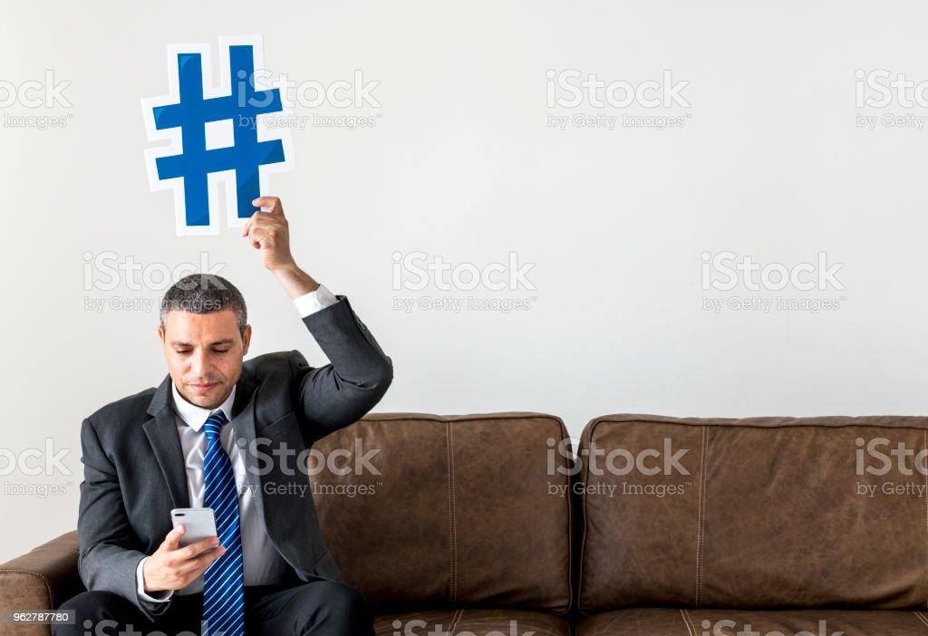 Empresário, sentado e segurando o ícone - Foto de stock de Adulto royalty-free