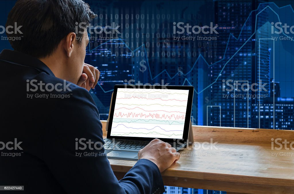 Businessman sitting and using computer laptop showing trading graph stock photo