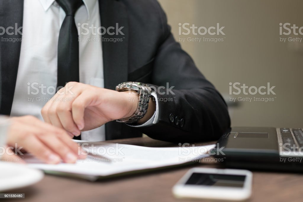 Businessman sitting at coffee shop. is looking at watch stock photo