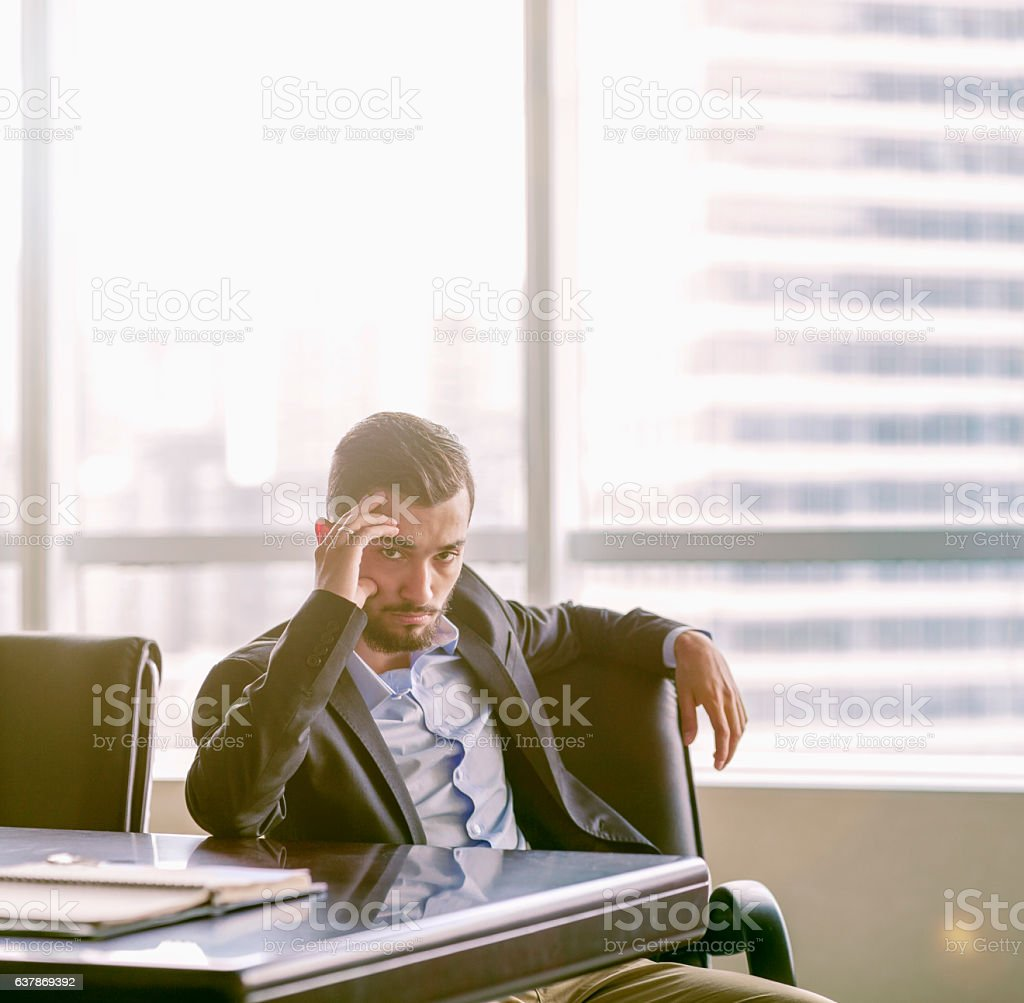 Businessman sitting at conference table in office stock photo