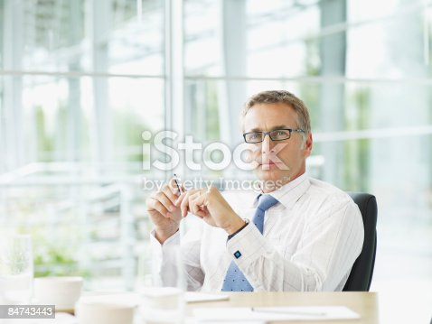 530281723istockphoto Businessman sitting at conference table 84743443