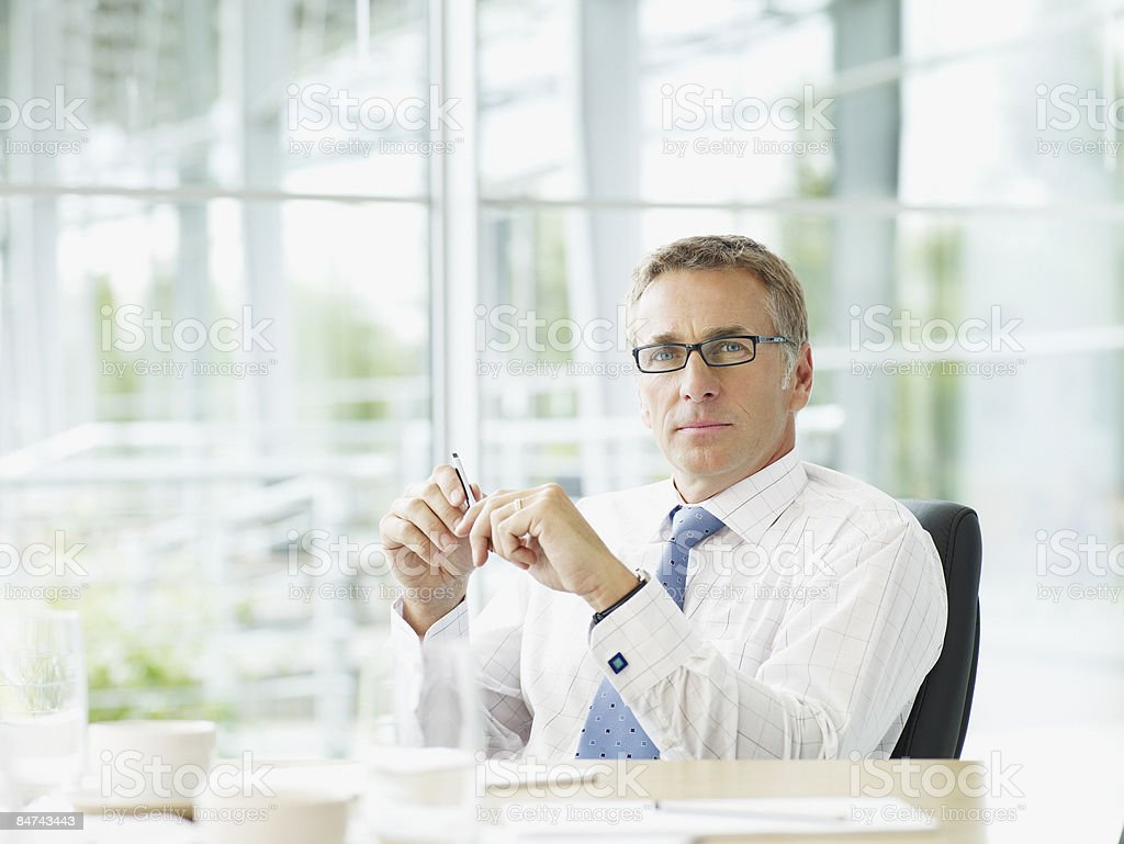 Businessman sitting at conference table stock photo
