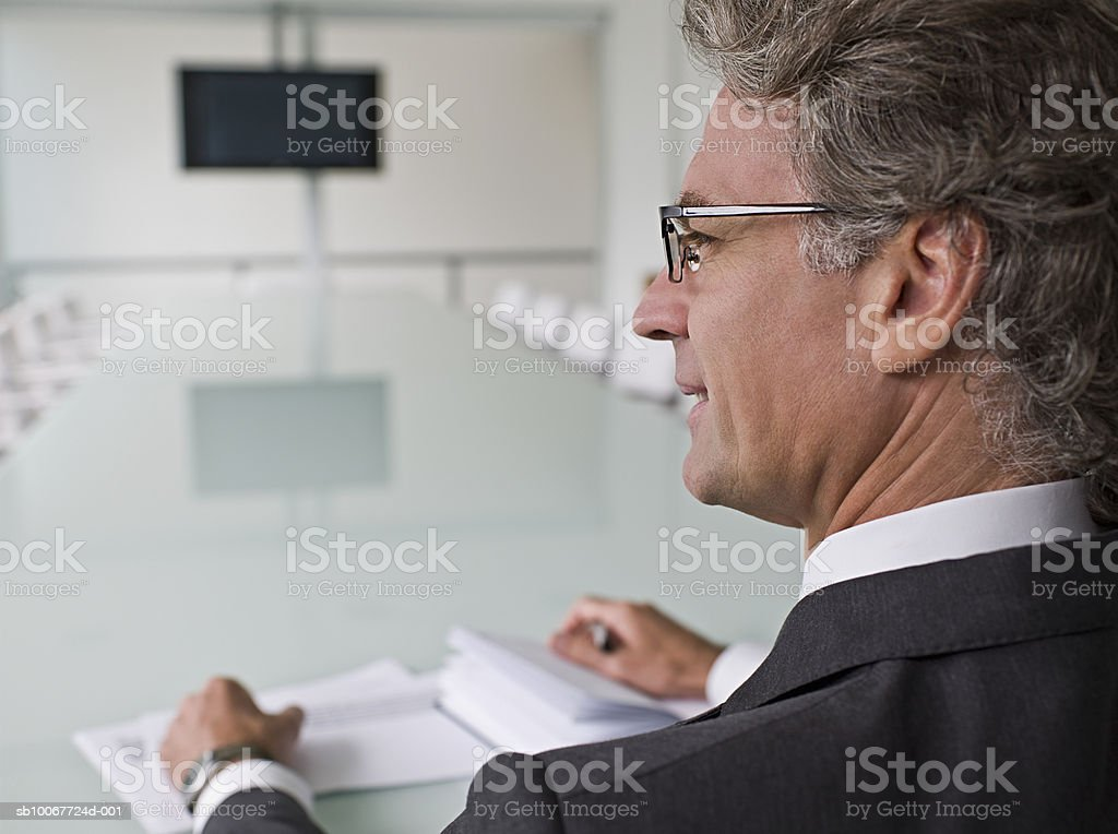 Businessman sitting at conference table with papers royalty-free stock photo