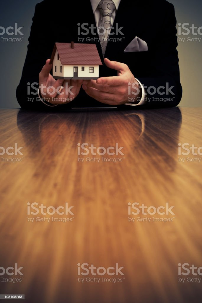 Businessman Sitting at Desk and Holding Model House royalty-free stock photo