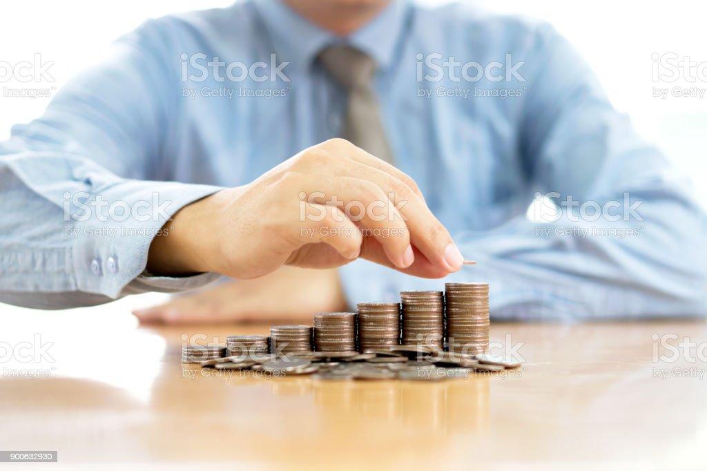 Geschäftsmann, sitzen am Schreibtisch und Stapeln von Münzen – Foto