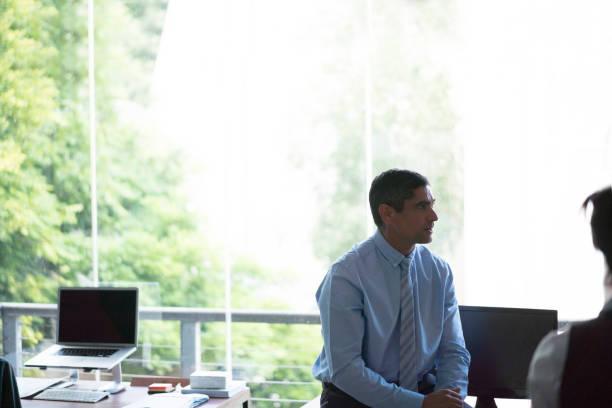 Geschäftsmann sitzt am Schreibtisch durch Fenster im Büro – Foto