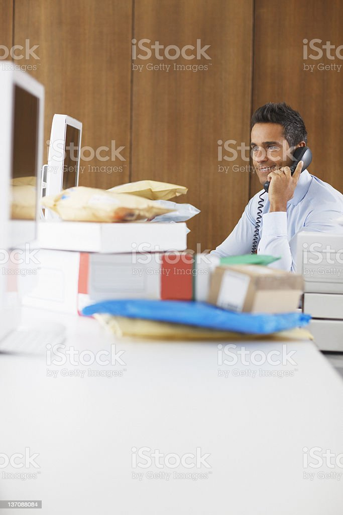 Businessman sitting at desk covered in packages royalty-free stock photo