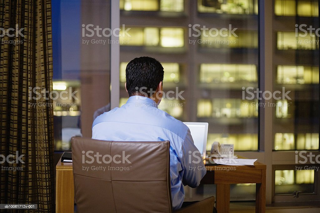 Businessman sitting at desk in hotel room, using laptop, rear view royalty free stockfoto