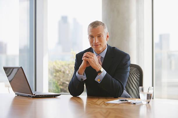 uomo d'affari seduto alla scrivania in ufficio - amministratore delegato foto e immagini stock