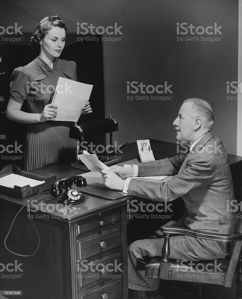 Businessman sitting at desk talking to secretary (B&W) stock photo