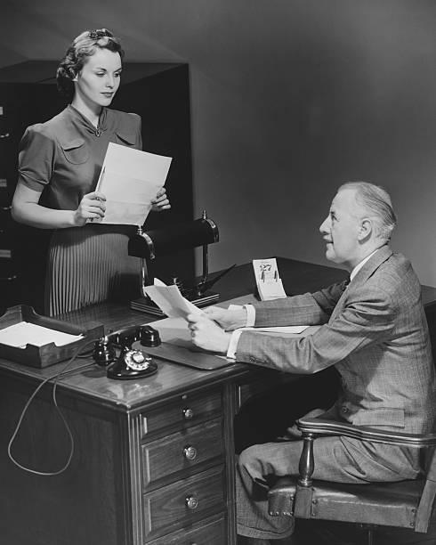 Empresário sentando na mesa falando ao Secretário & (B W - foto de acervo