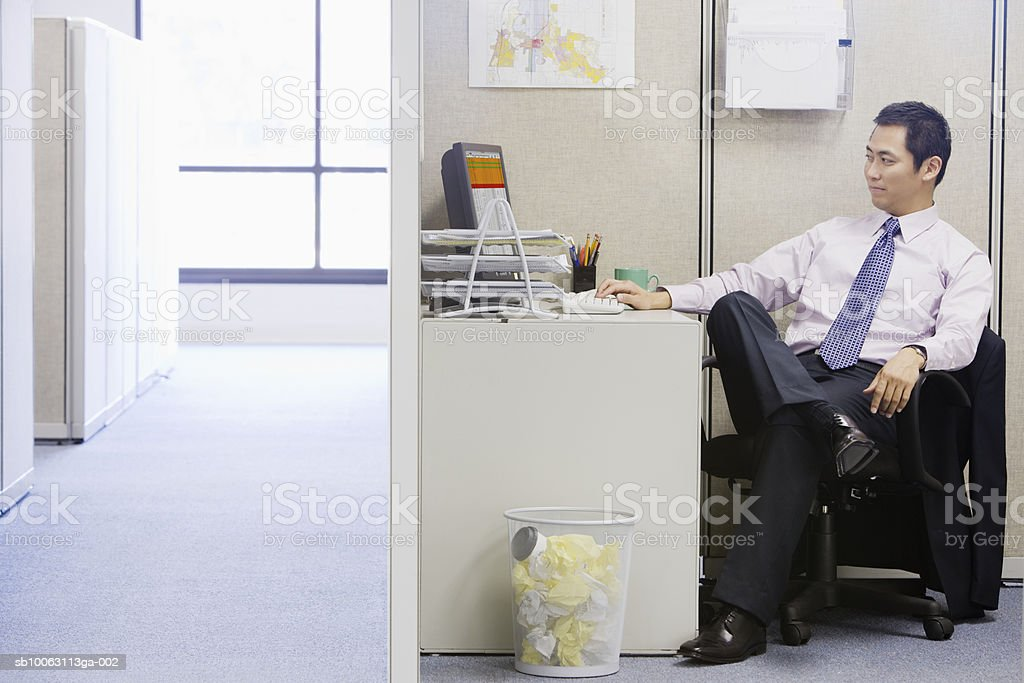 Businessman sitting at desk using computer Lizenzfreies stock-foto