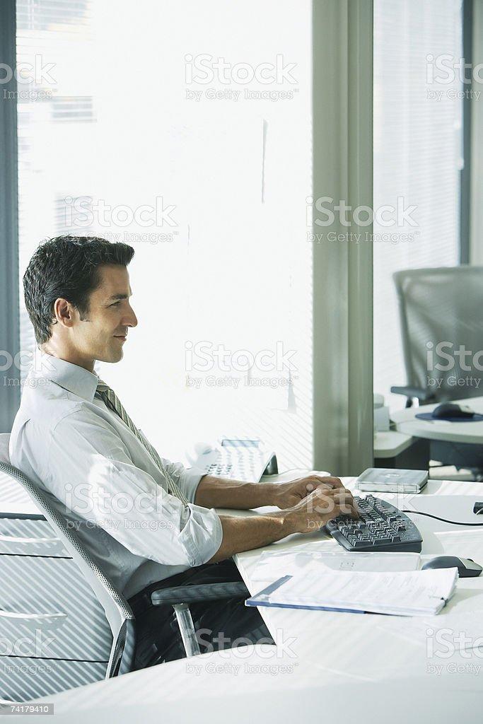 Empresário sentado à mesa de trabalho com computador e a sorrir foto de stock royalty-free