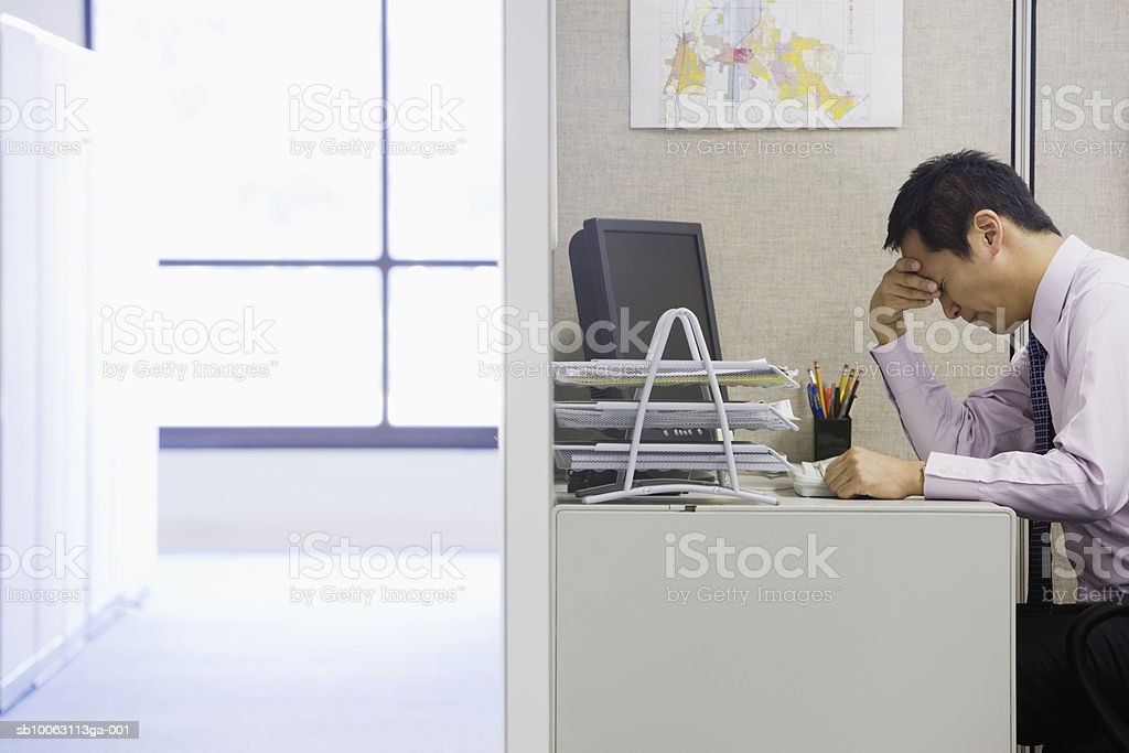 Businessman sitting at desk with head in hands, side view royalty-free stock photo