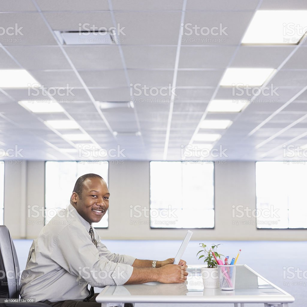 Businessman sitting at desk with laptop, smiling, portrait foto de stock libre de derechos
