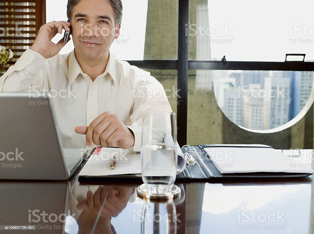 Businessman sitting at desk with laptop using mobile phone foto de stock royalty-free