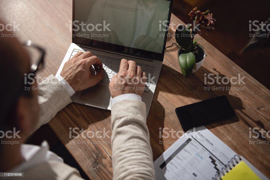彼の机の上に座って、オフィスでラップトップを使用しているビジネスマン ストックフォト