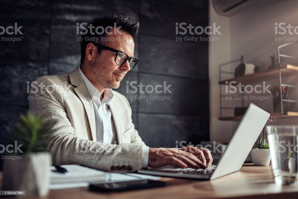 Businessman sitting at his desk and using laptop in the office Businessman wearing linen suit and eyeglasses sitting at his desk by the window and using laptop in the office Accountancy Stock Photo