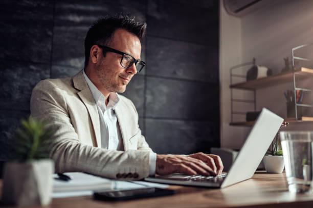 homem de negócios que senta-se em sua mesa e usando o portátil no escritório - business man - fotografias e filmes do acervo