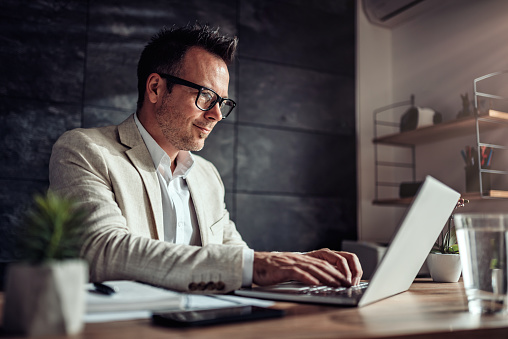 Businessman Sitting At His Desk And Using Laptop In The Office Stock Photo - Download Image Now