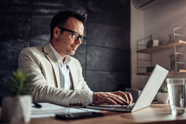 Businessman sitting at his desk and using laptop in the office Businessman wearing linen suit and eyeglasses sitting at his desk by the window and using laptop in the office business laptop stock pictures, royalty-free photos & images