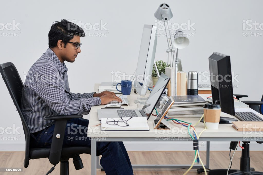 Businessman sitting at his workplace Serious businessman in eyeglasses sitting at his workplace and typing on computer keyboard at office Adult Stock Photo