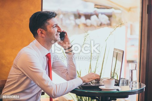 Businessman sitting at table in cafe talk on mobile phone.
