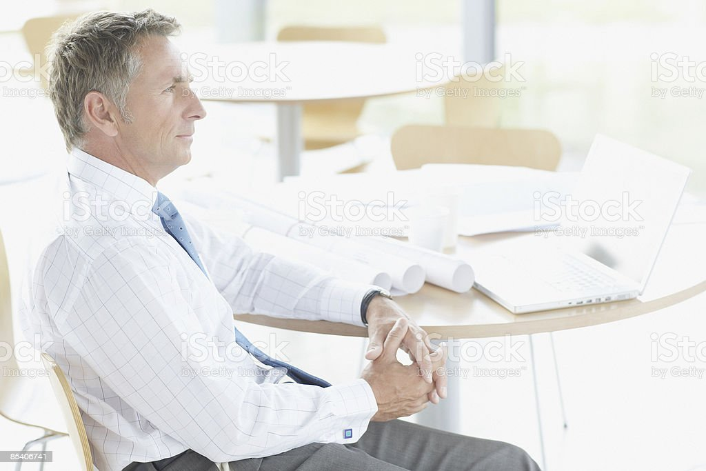 Businessman sitting at table with blueprints royalty-free stock photo