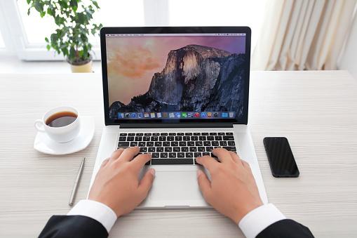businessman sitting at the MacBook Pro Retina with OSX Yosemite
