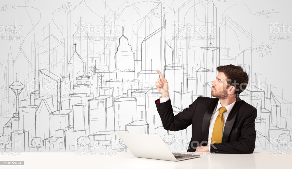 Businessman sitting at the white table with hand drawn buildings stock photo