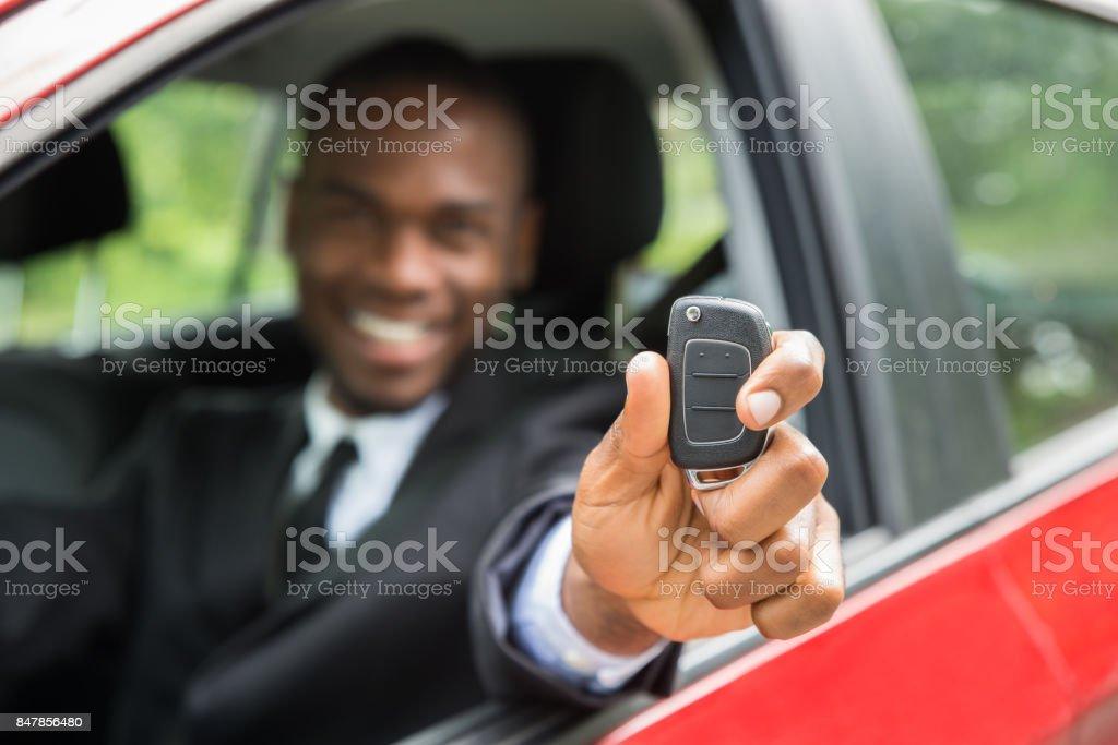 Businessman Sitting In A Car Showing Car Key stock photo