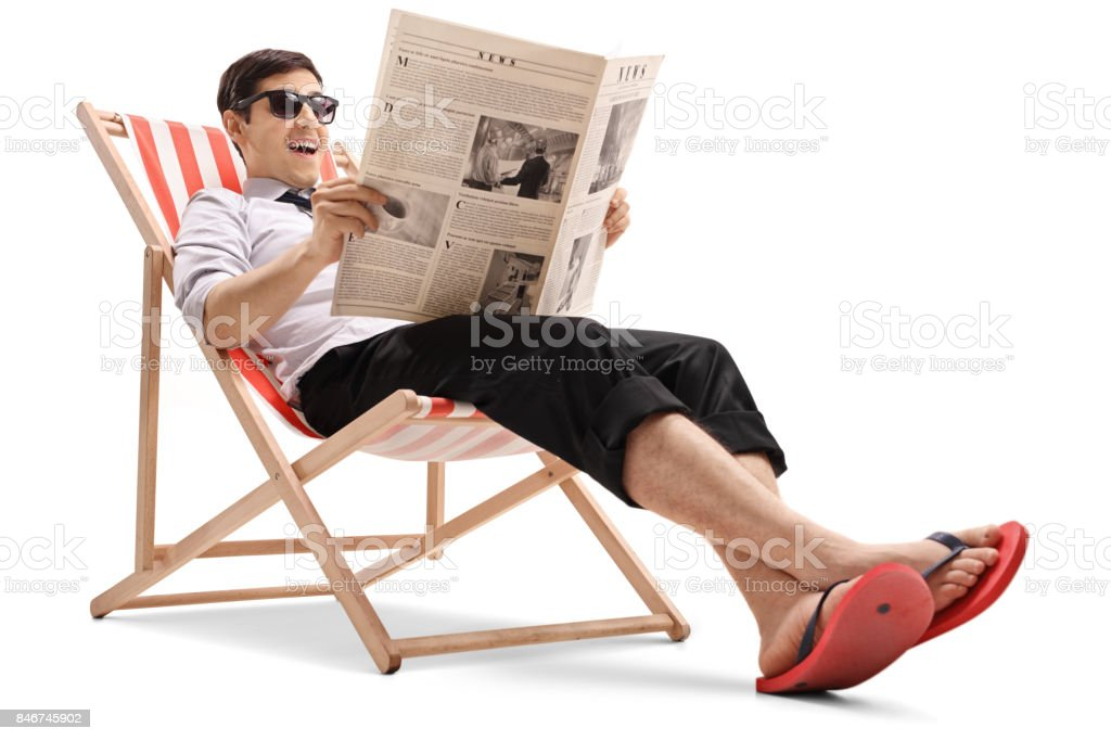 Businessman sitting in a deck chair and reading a newspaper stock photo