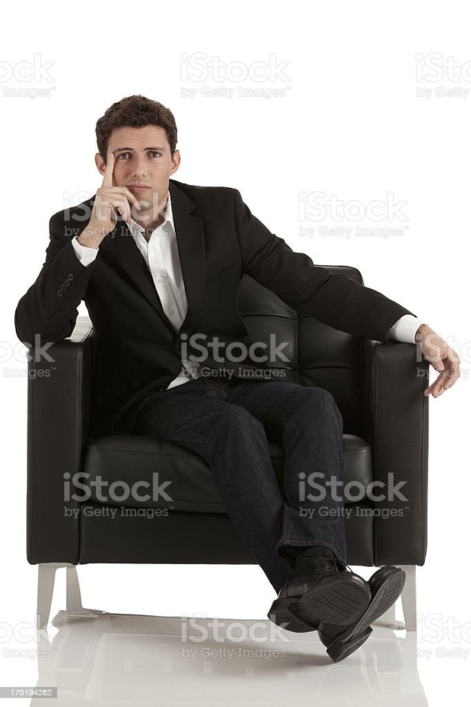 Businessman sitting in an armchair and thinking royalty-free stock photo