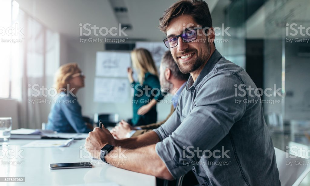 Businessman sitting in board room during presentation stock photo