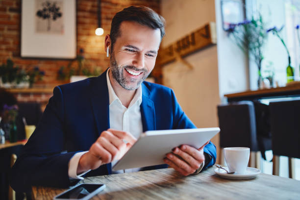 Businessman sitting in cafe looking at tablet during phone call through wireless headphones Businessman sitting in cafe looking at tablet during phone call through wireless headphones bluetooth stock pictures, royalty-free photos & images