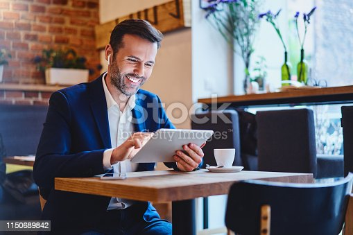 Businessman sitting in cafe using tablet and talking through wireless headphones