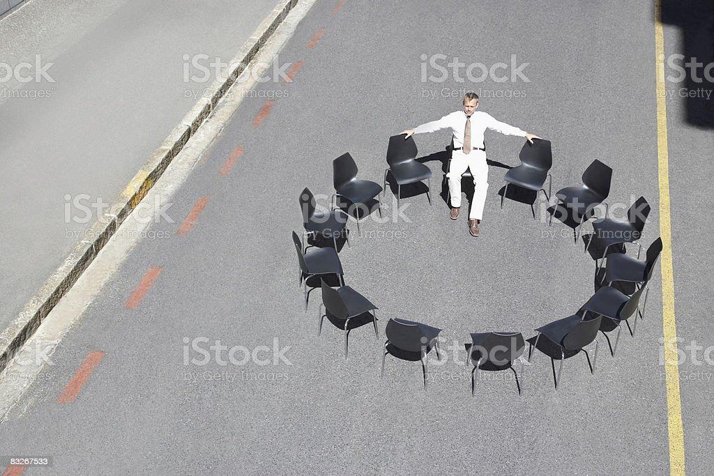 Businessman sitting in circle of office chairs in roadway royaltyfri bildbanksbilder
