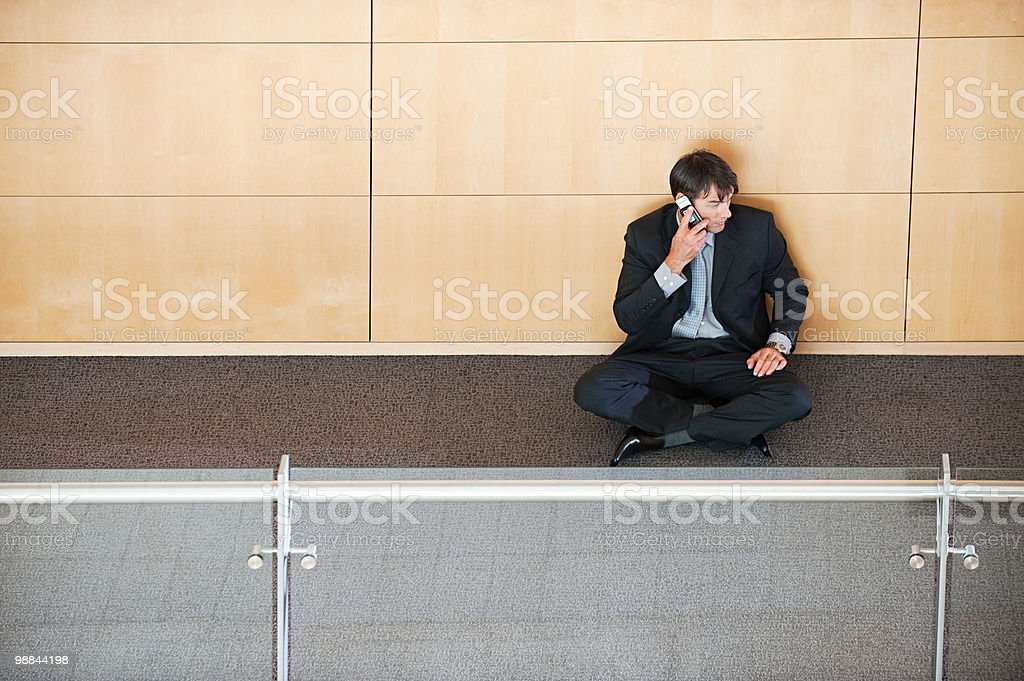Businessman sitting in corridor using cellphone royalty-free stock photo