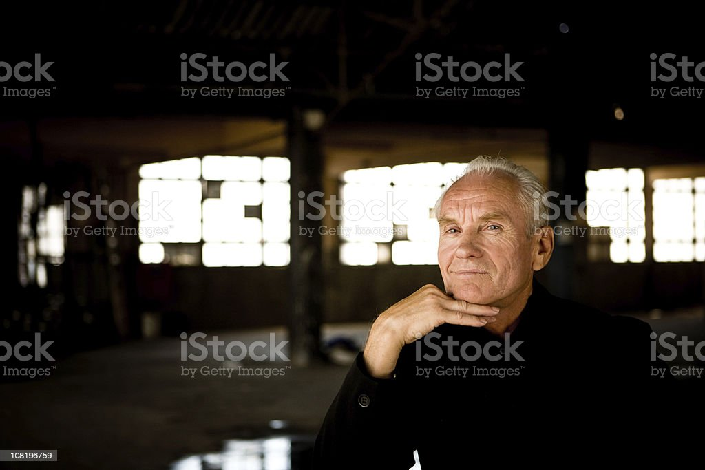 Businessman Sitting in Empty Warehouse royalty-free stock photo