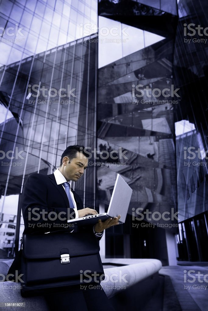 Businessman sitting in front of all-glass modern building royalty-free stock photo