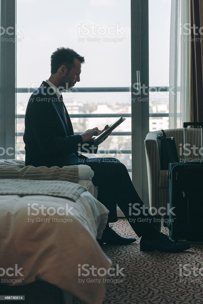 Businessman sitting in hotel room and using digital tablet Silhouette of businessman wearing suit sitting on bed in hotel room and using a digital tablet with city scape from the window. 2015 Stock Photo