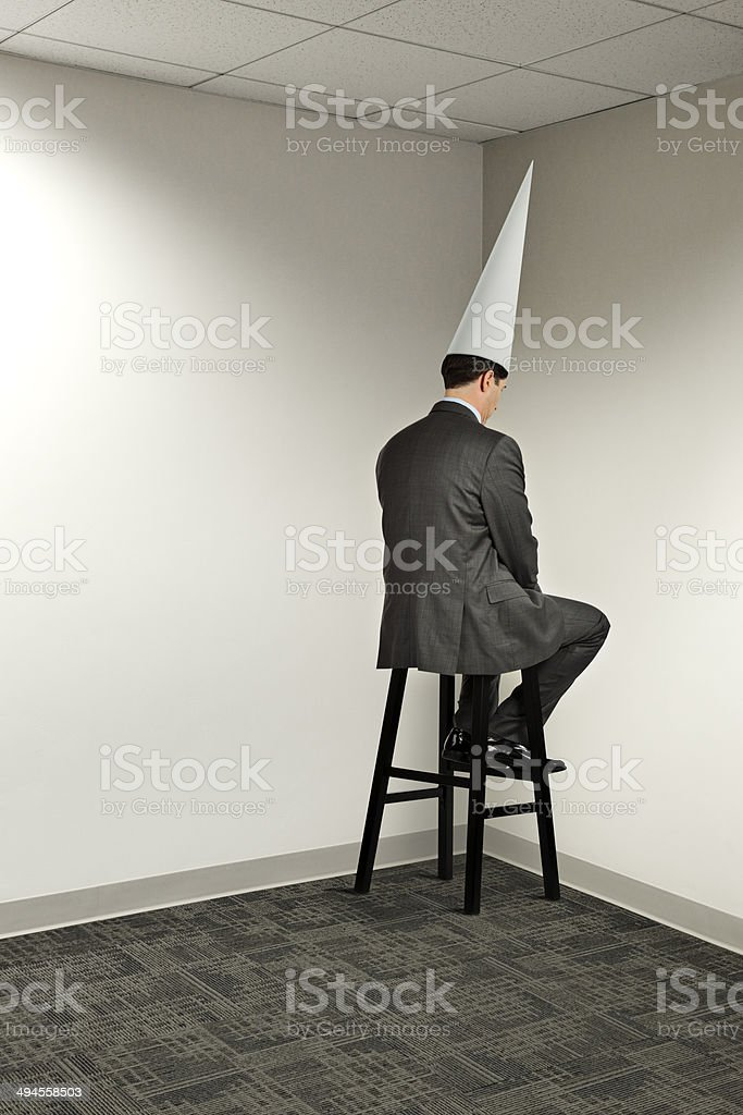 Businessman Sitting In Office Corner Wearing Dunce Cap stock photo