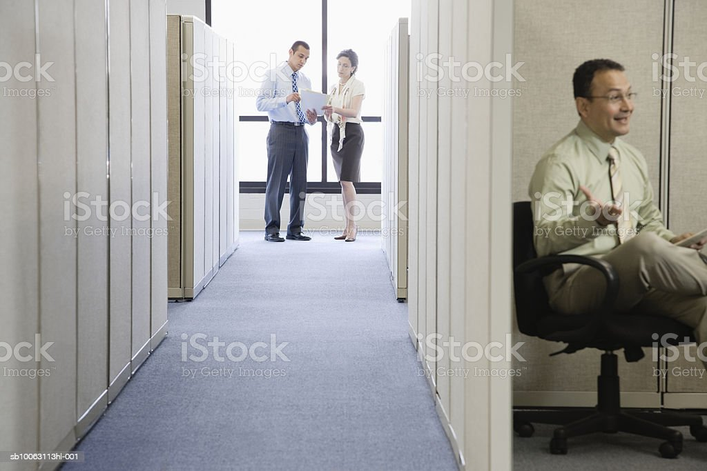 Businessman sitting in office cubical, colleagues discussing in background photo libre de droits