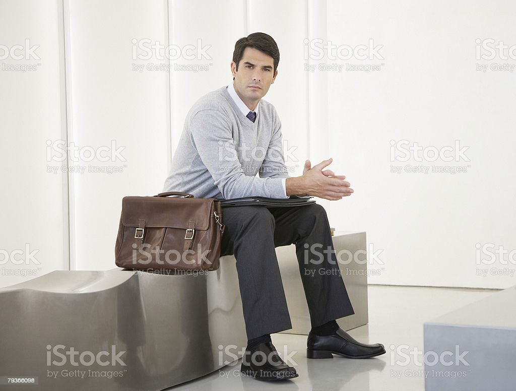 Businessman sitting in office lobby looking at camera 免版稅 stock photo